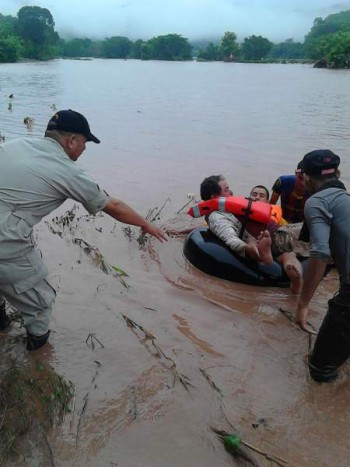 Photo of a responder assisting a person in the Ulua River.